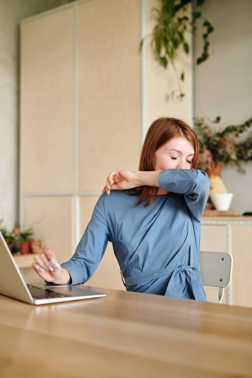 woman in blue long sleeve shirt using macbook air on brown wooden table