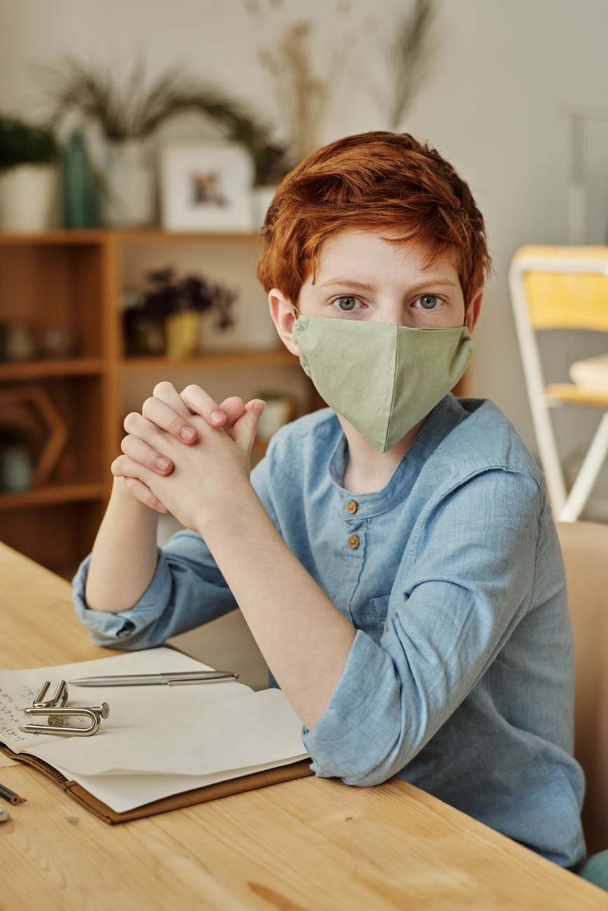 boy in blue long sleeve shirt wearing face mask