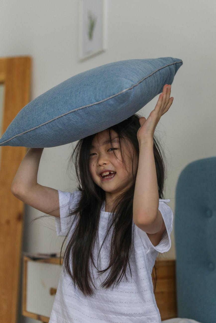 happy asian girl with pillow over head