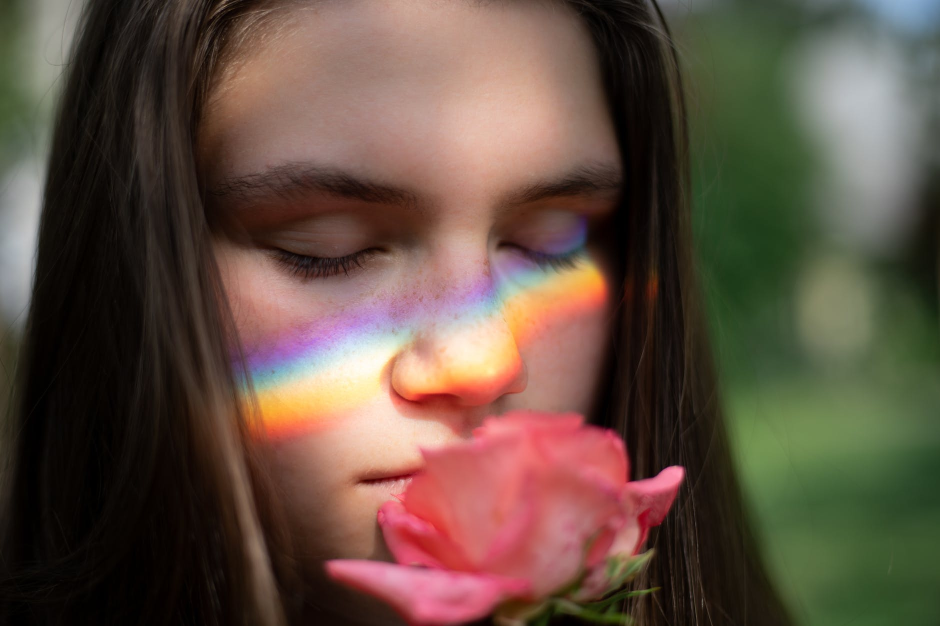 close up photography of woman smelling pink rose