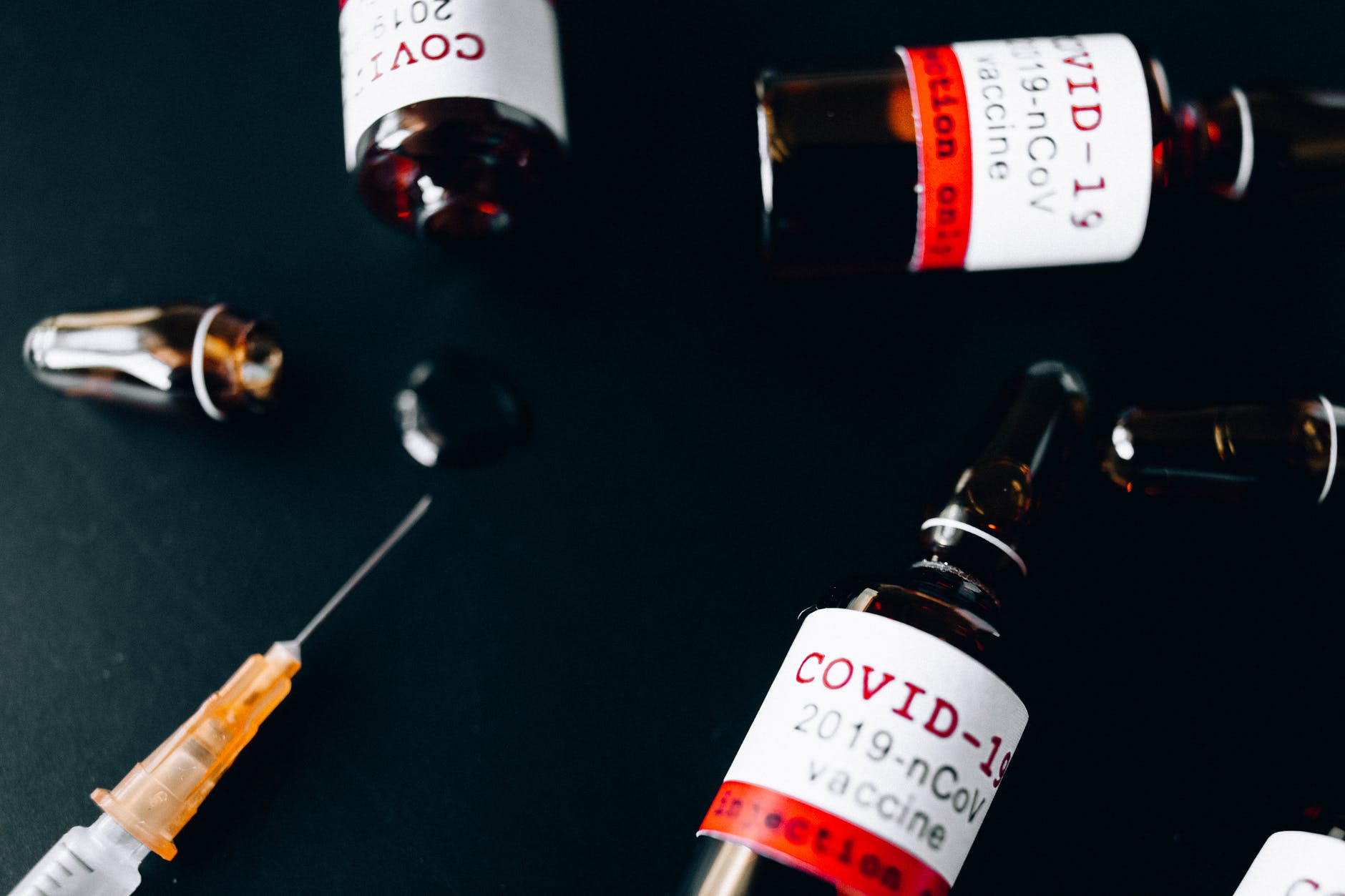 three small glass bottle and a syringe
