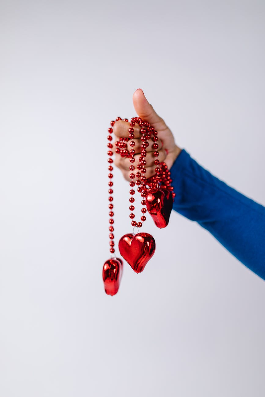 person holding red beaded necklaces