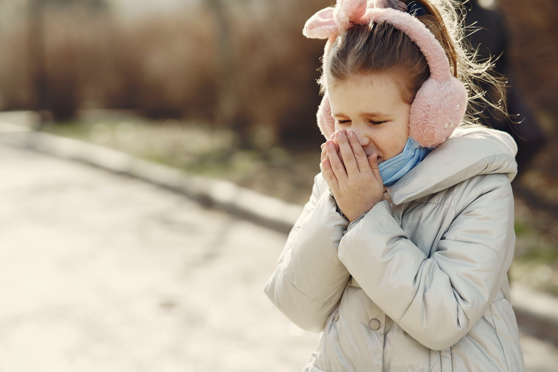 little girl sneezing while walking in park