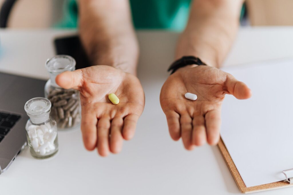crop doctor showing pills to patient in clinic