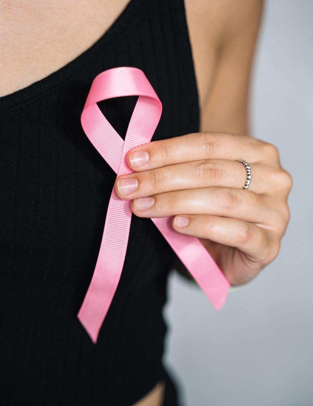 woman in black tank top holding pink ribbon