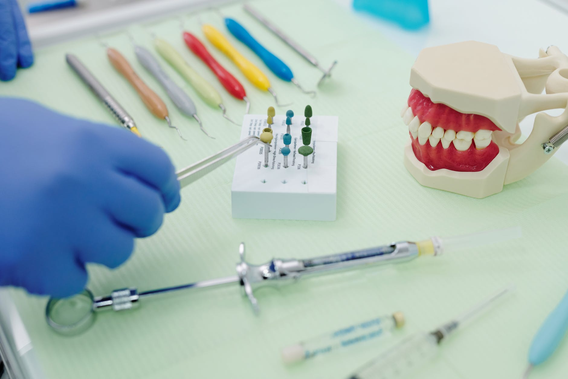 crop unrecognizable stomatologist with tweezers and dental tools in clinic