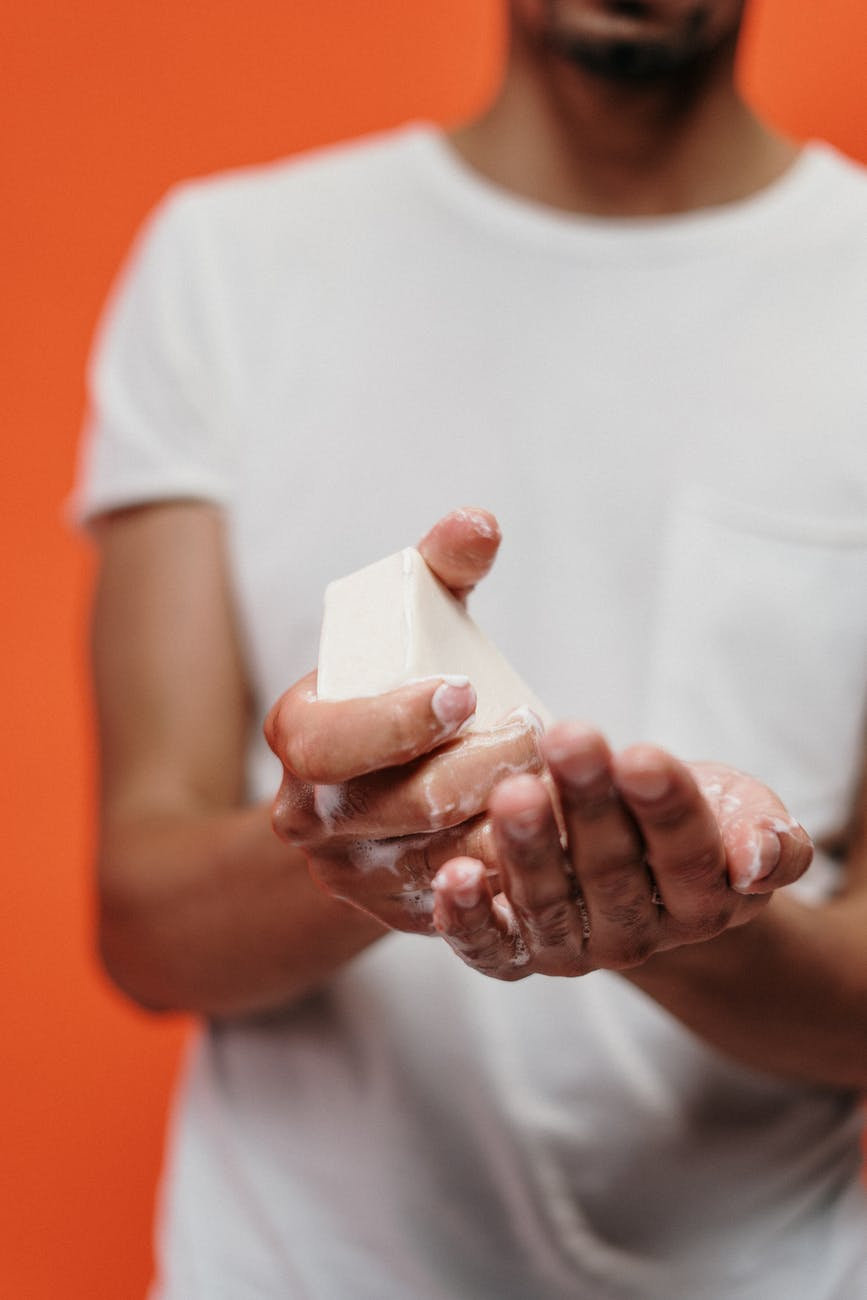 person in white crew neck t shirt holding bar soap