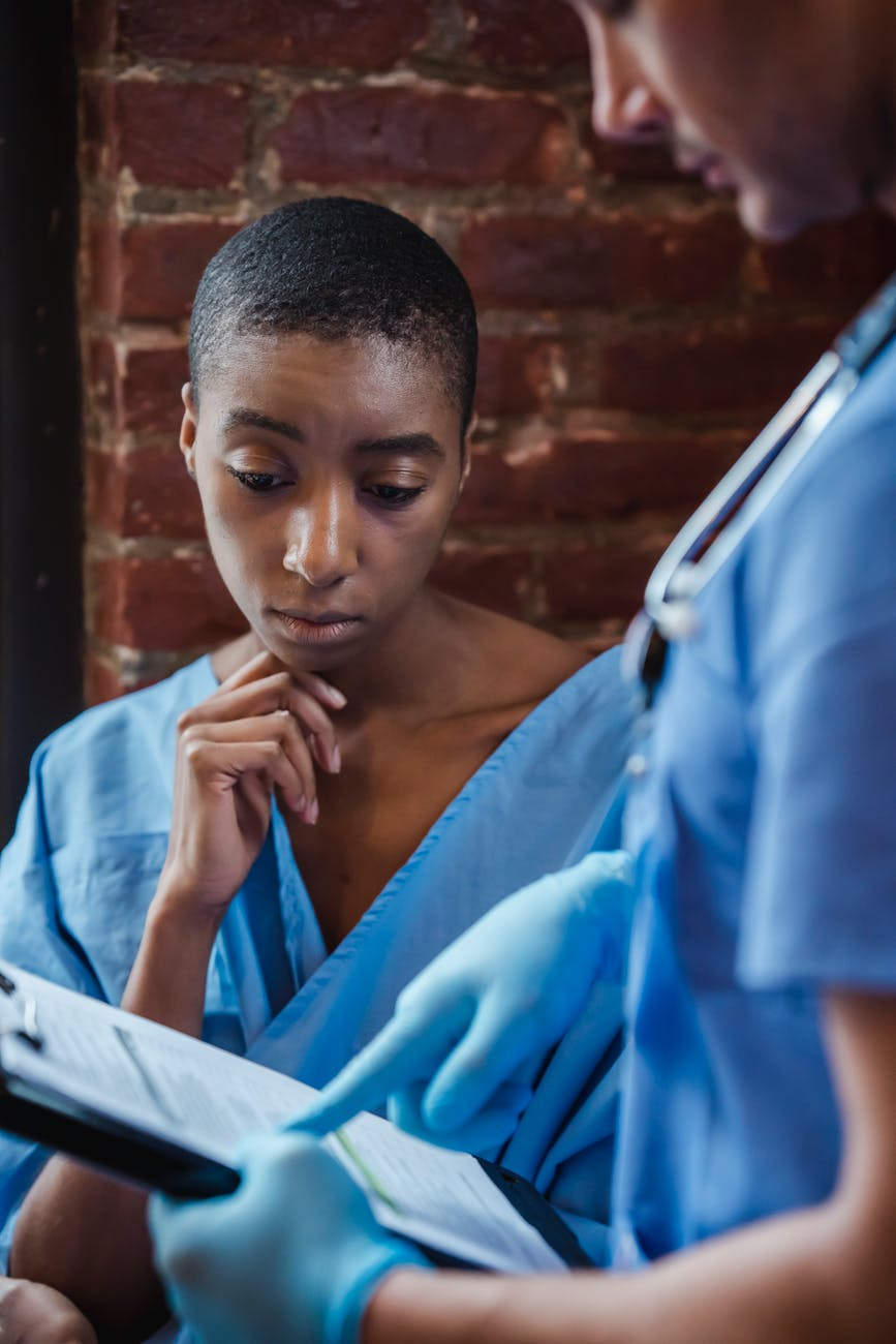 pensive black patient discussing diagnosis with doctor in hospital