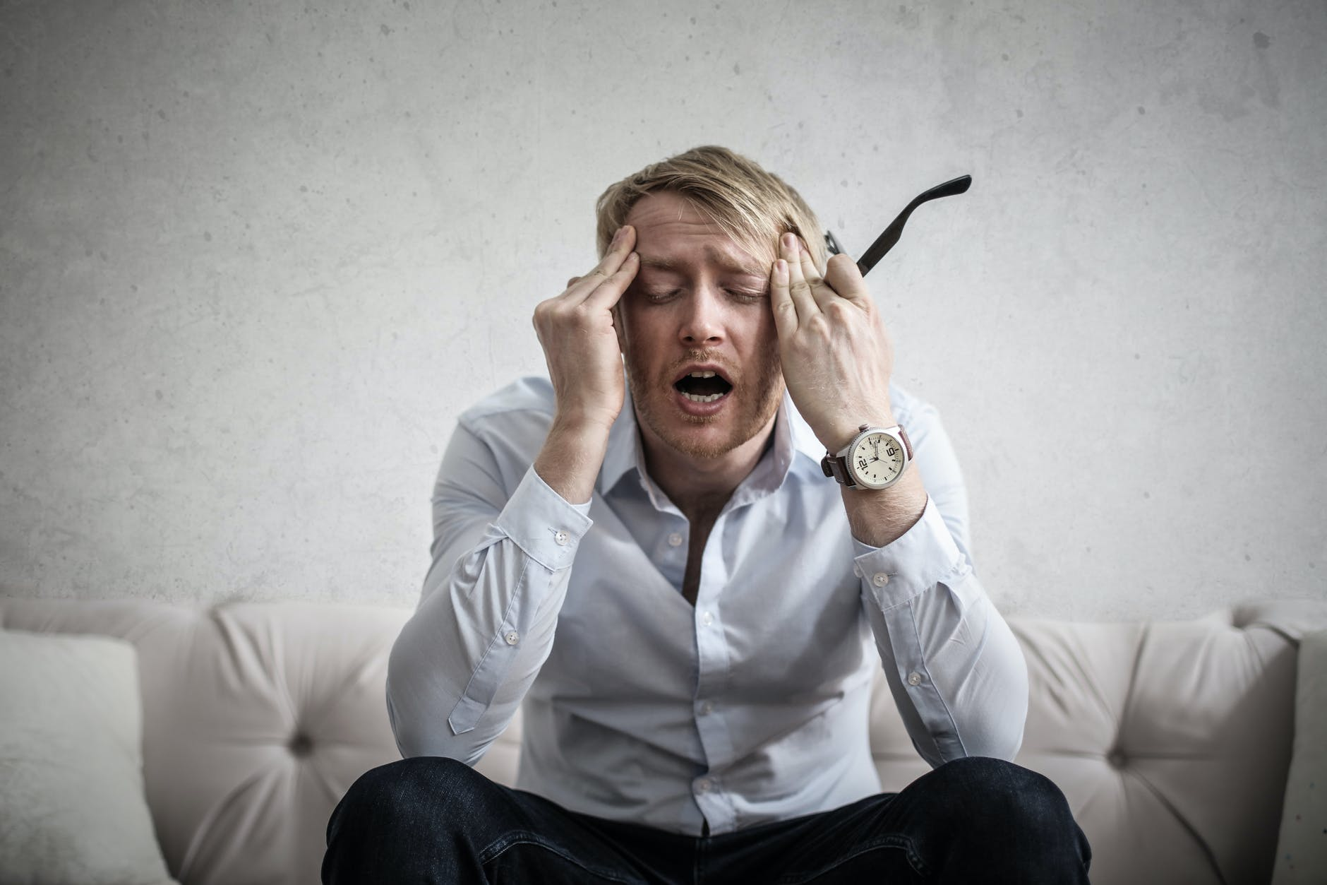 photo of man touching his head