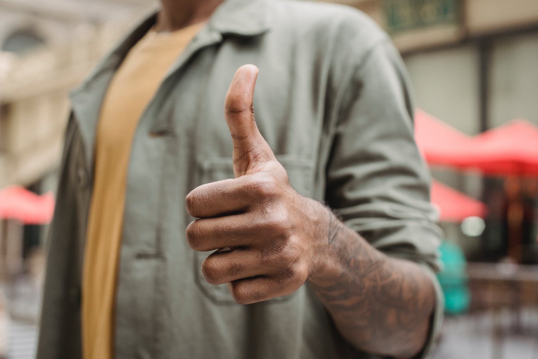 anonymous ethnic man demonstrating thumb up sign on street