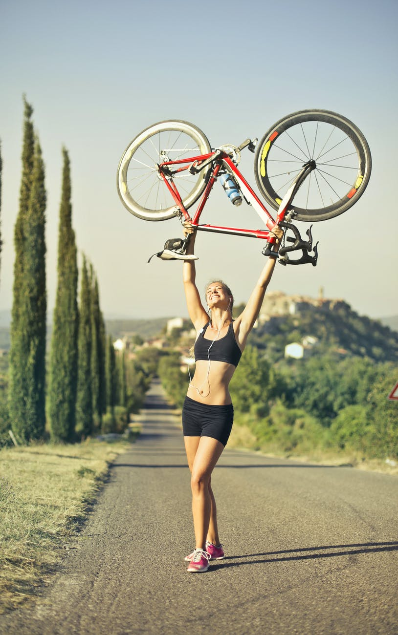woman carrying a bicycle under the sunlight