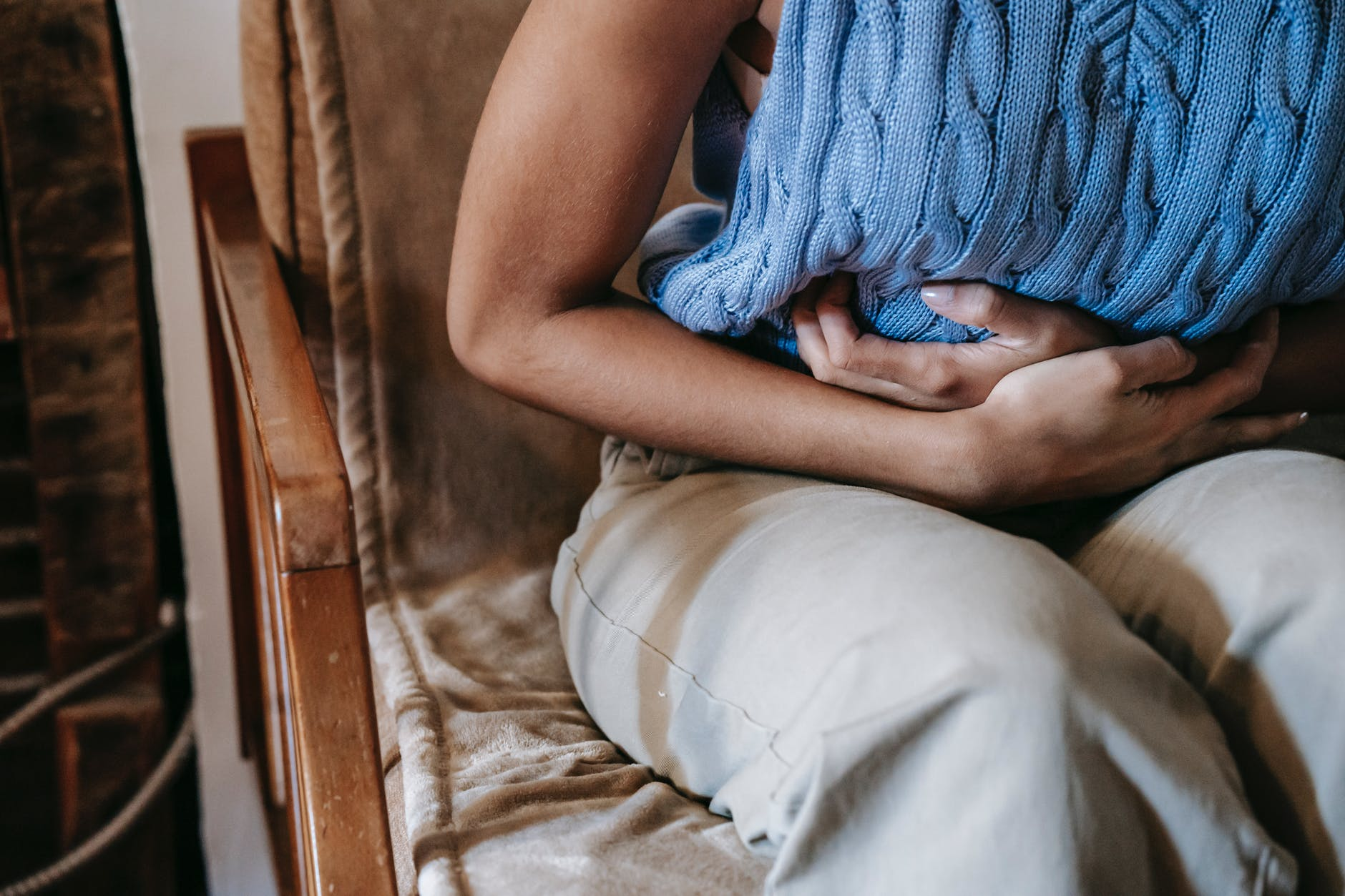 crop woman in pain on sofa