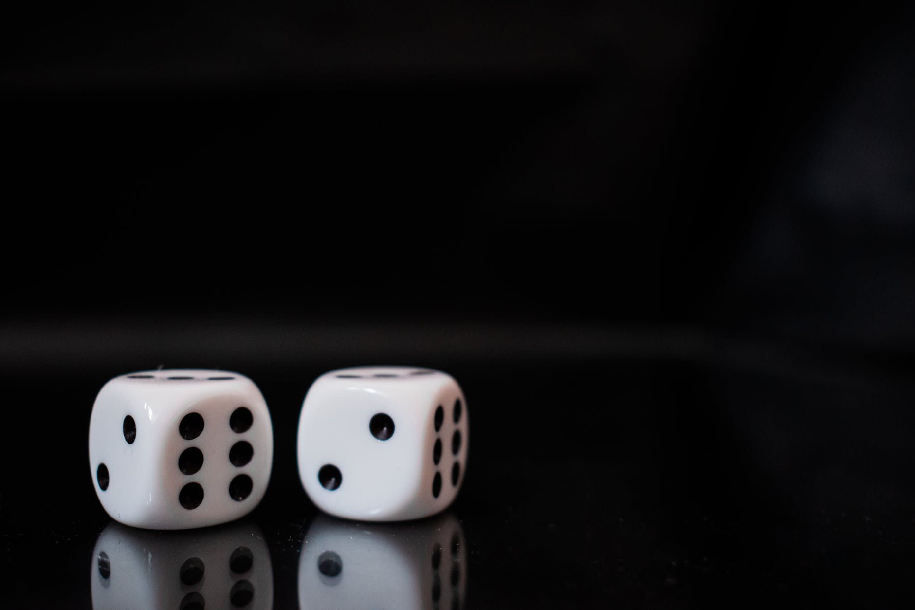 close up view of two white dices on black surface