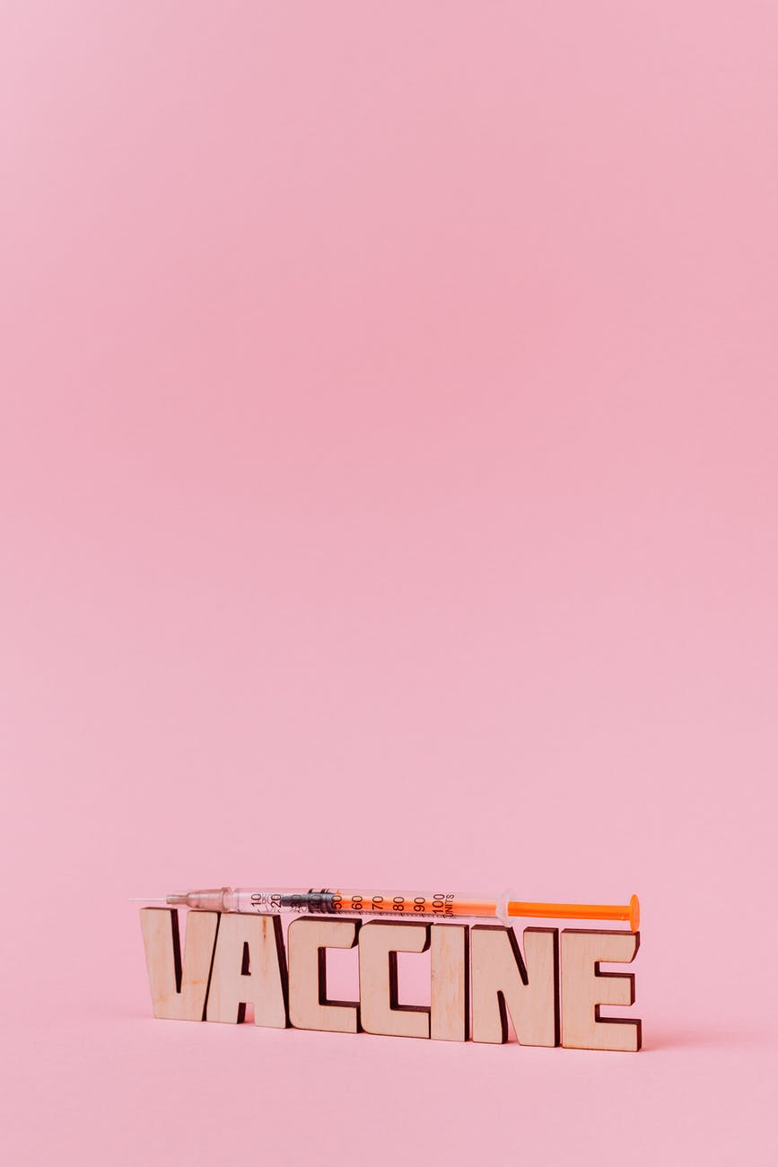 a syringe and vaccine lettering text on pink background